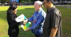 Penyerahan penghargaan oleh Asisten I John Palandung kepada anggota KORPRI Sulut.