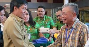 Walikota Manado Dr Ir GSV Lumentut SH DEA saat menyerahkan penghargaan kepada Prof Dr Lucky Sondakh