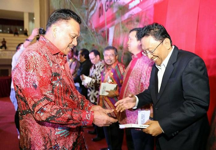 Sekprov Sulut Edwin Silangen SE MS saat menerima buku hasil karya Gubernur Sulut Olly Dondokambey SE