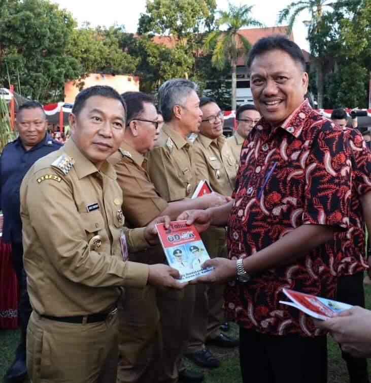 Bupati Kabupaten Minahasa Tenggara James Sumendap SH saat menerima buku 3 Tahun ODSK Pimpin Sulut yang diserahkan langsung Gubernur Olly Dondokambey SE, Selasa (12/02/2019)