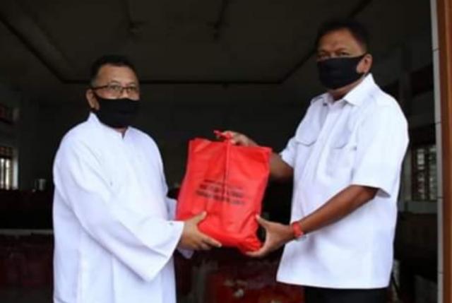 Gubernur Olly Dondokambey SE saat menyerahkan bantuan paket sembako di Gereja Katolik Paroki Ratu Rosari Tuminting Manado, Rabu (22/04/2020) pagi
