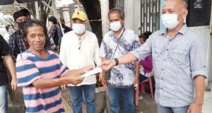 Ketua PWI Cabang Sulut Voucke Lontaan saat memberi masker kepada warga yang tidak memakai masker, Jumat (10/07/2020)
