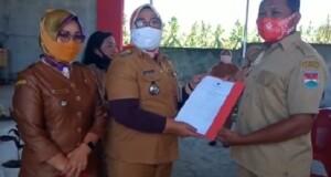 Didampingi Hukum Tua  Hj Citra Kawulusan, Camat Belang Munira Bin Ali menyerahkan SK  Bupati Mitra kepada Aparatur Desa dan BPD Tababo Selatan, Senin (14/09/2020)