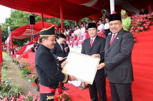 Gubernur Olly Dondokambey SE saat menyerahkan penghargaan kepada Wakil Walikota Maurits Mantiri