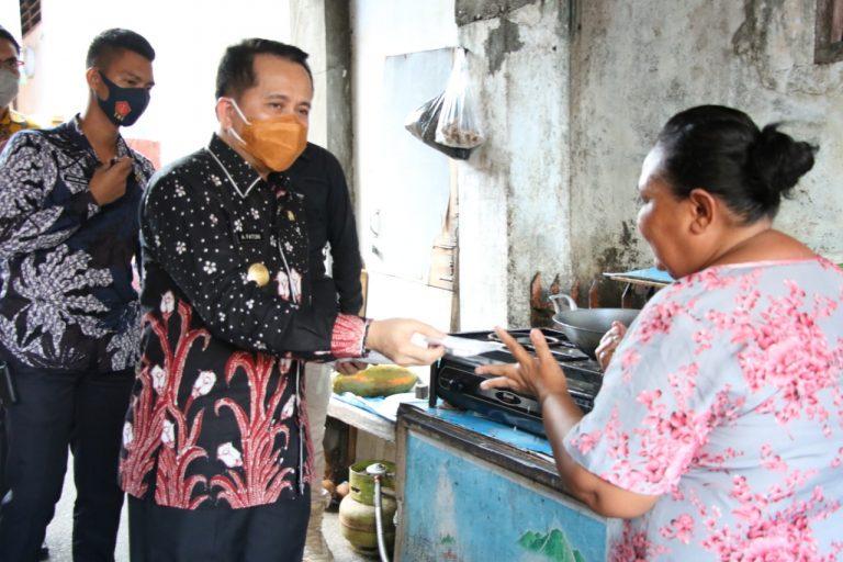 Pjs Gubernur Agus Fatoni saat membagi-bagikan masker kepada warga di Manado.