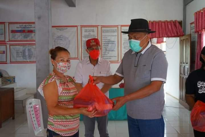 Gubernur Olly Dondokambey SE didampingi Bupati Minahasa ROR menyerahkan bantuan secara simbolis kepada warga korban bencana banjir di Papakelan Minahasa, Kamis (31/12/2020)
