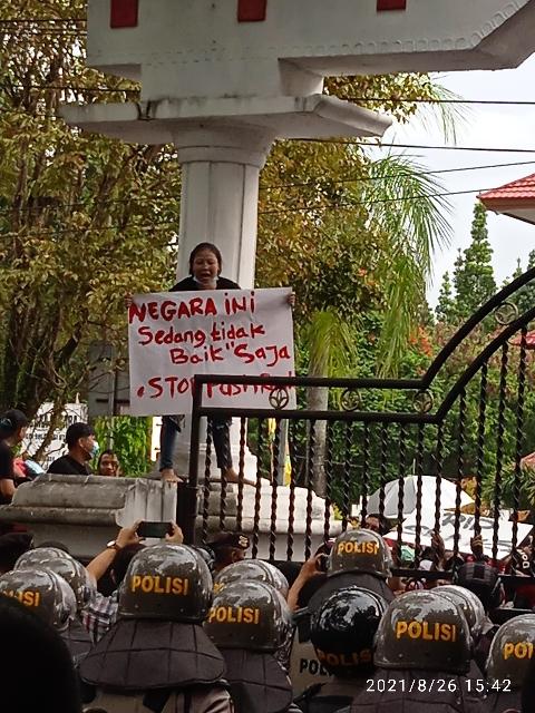 Salah seorang pendemo naik ke atas sambil membentangkan tulisan saat demo damai di depan Kantor Gubernur Sulut, Kamis (26/08/2021) siang.